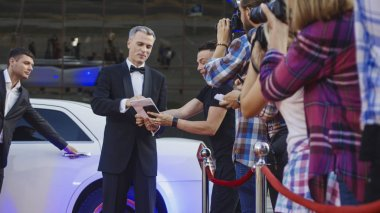 Adult celebrity giving autographs on red carpet