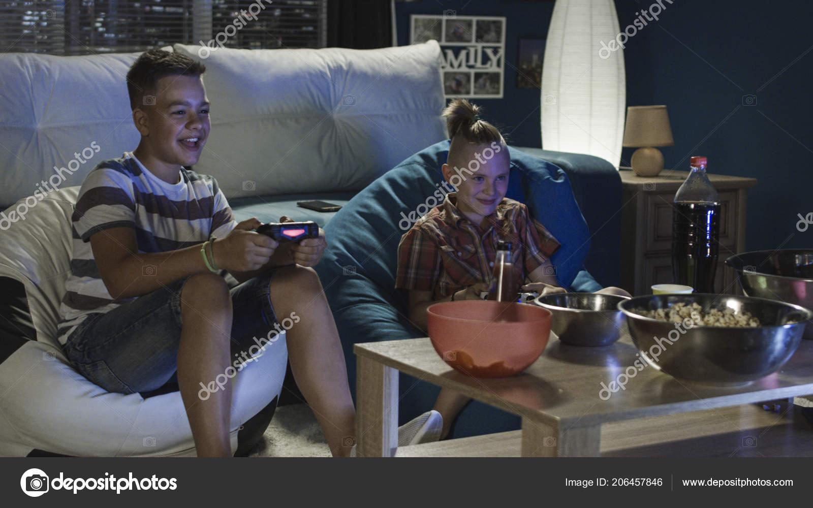 Teen boys playing videogame together on sofa — Stock Photo ...