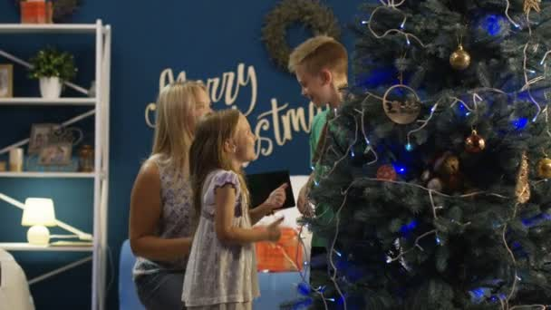 Happy adult woman with little boy and girl spending time in love together decorating fir tree and having fun before Christmas