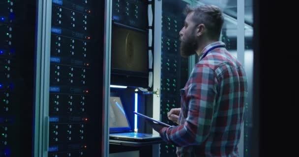Člověk pomocí přenosného počítače na farmě těžby v datovém centru