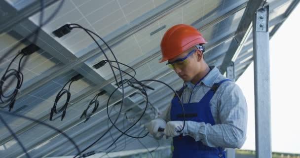 Arbeiter verbinden Drähte von Sonnenkollektoren