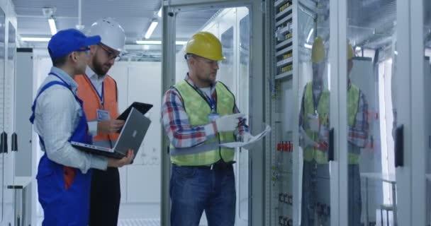 Elektriker arbeiten in der Leitwarte