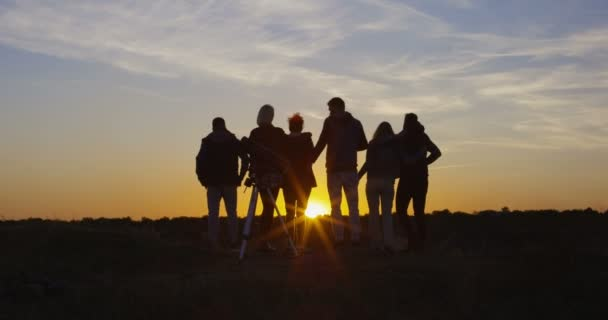 Friends together in the setting sun cheering