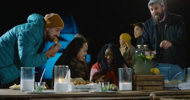 Skupina multietnické přátel, mluvit, jíst a pít