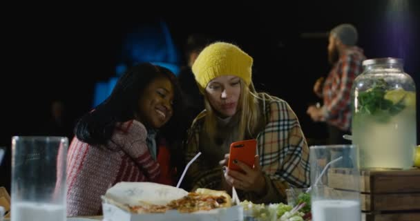 Female best friends looking at their smartphone