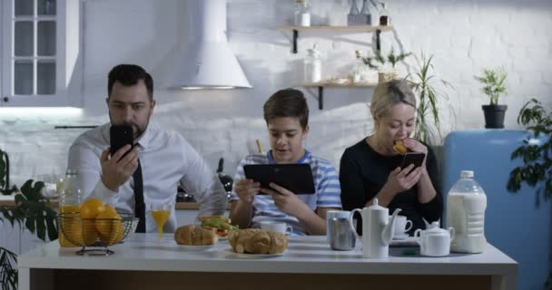 Medium shot of a family sitting side by side at the kitchen table and watching their smartphones and tablets
