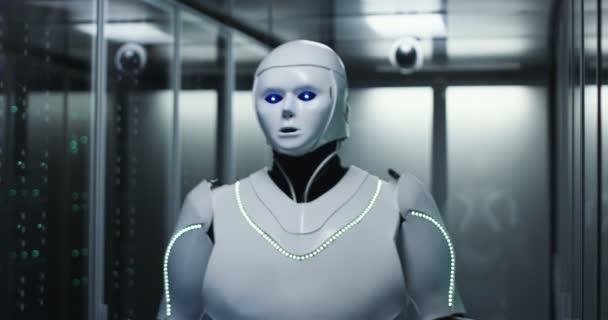 Střední střílel humanoidní robot kontrolu serverů v datovém centru při držení tabletu