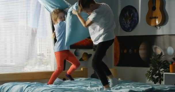 Boy and girl playing pillow fight on bed