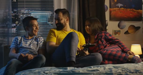 Father with son and daughter sitting on bed