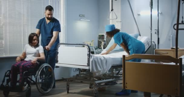 Male nurse and doctor lifting patient into his bed