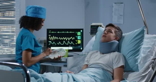 Nurse feeding teenage patient