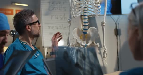 Doctors examining cervical spine x-ray