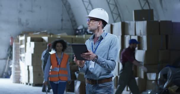 Vedoucí skladu dohlíží na zaměstnance