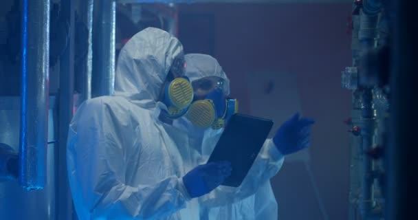 Wissenschaftler in Schutzanzügen bei Wartungsarbeiten