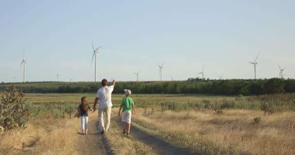 Vater zeigt Kindern Windmühlen