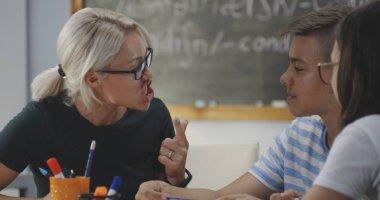 Teacher explaining to pupils in a classroom