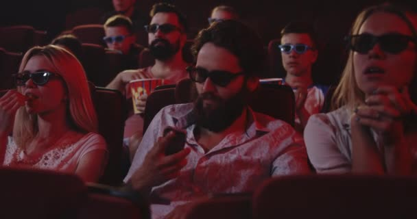 Mann telefoniert in einem Kino