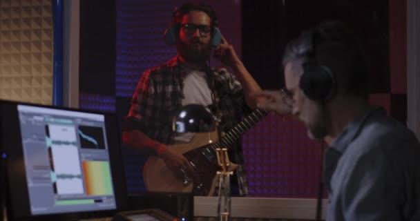 Sound engineer instructing guitarist