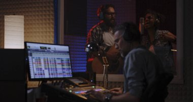 Medium shot of vocalist guitarist and sound engineer working in studio stock vector