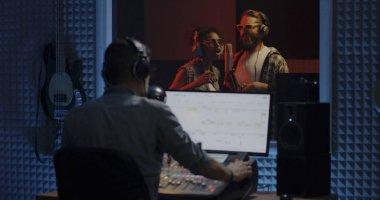 Medium shot of singers and sound engineer working in studio stock vector