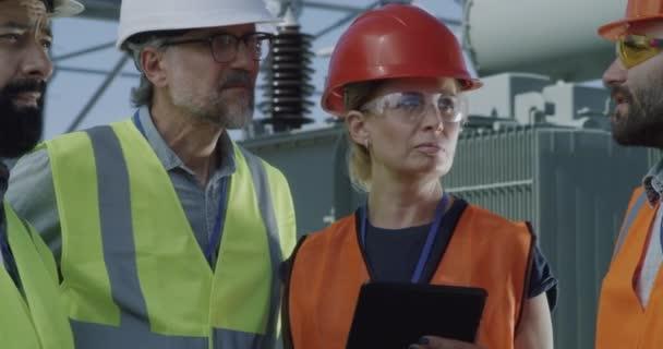 Ingenieurin diskutiert mit Männern über Daten auf dem Tablet