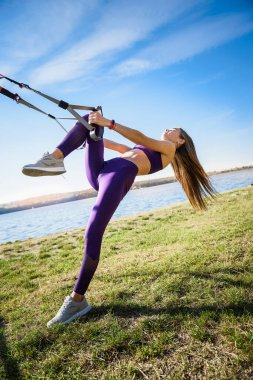 sport woman doing  training outdoors with TRX at daytime. Total body resistance exercises for her healhty lifestyle.