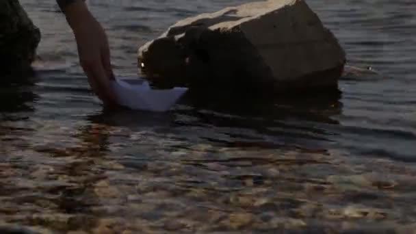 an einem sonnigen Tag ein Papierboot starten. transparentes Wasser, Strömung, Pfad zwischen Hindernissen.