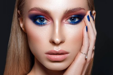 Beautiful woman portrait with blue glamour make up and blue nails