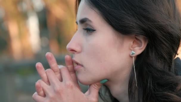 Pohled smutně mladých ženách krásné tvář, s očima červené od slz, opřel se zkříženými prsty