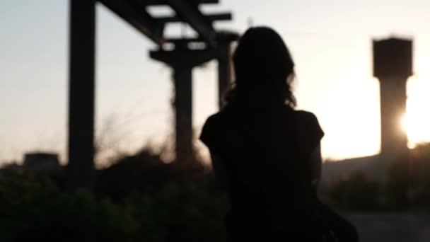 Rozostřený silueta mladé ženy, odchází do západu slunce