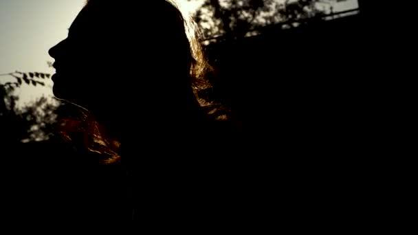 Silueta mladé ženy dotkne její vlasy, emotivně, pocit únavy