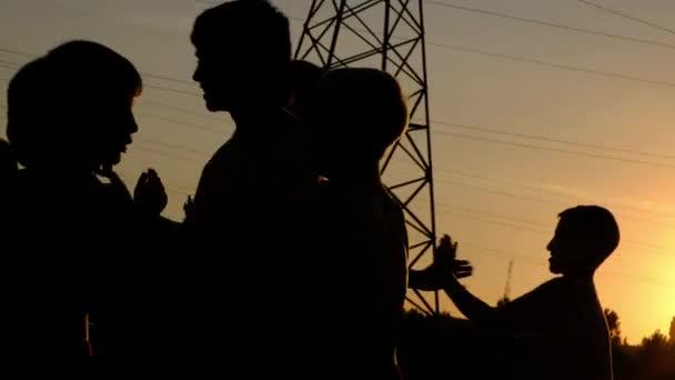 Siluette dei ragazzi giovani, jogging e competere su una formazione contro il tramonto