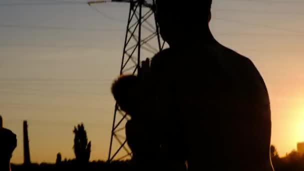 Siluette dei ragazzi giovani, fare jogging su una formazione contro il tramonto