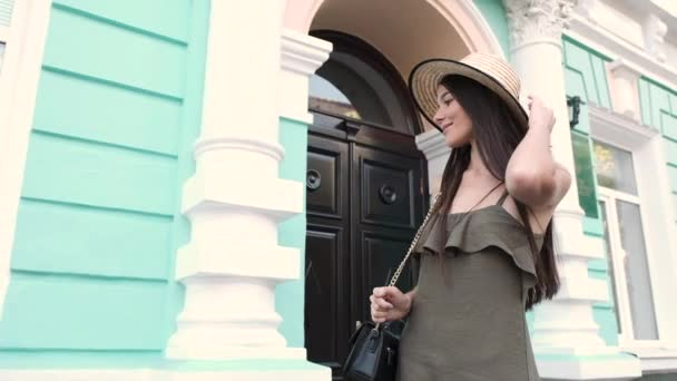 A young woman walks along the street while looking around. Slow motion