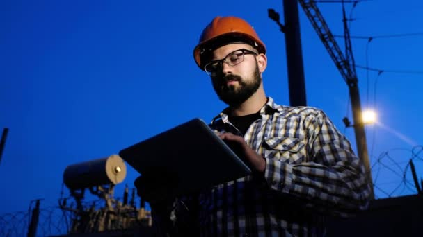 Energetické inženýr muž použít digitální Tablet. Elektrárna Wire Lines Network větrné elektrárny a jejich údržba. Modrá hodina při západu slunce