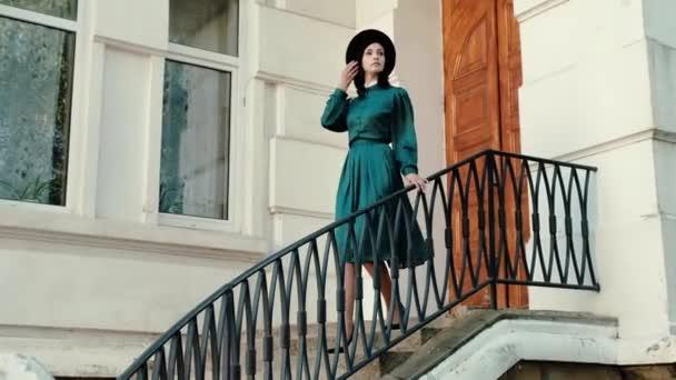 ein Mädchen in Vintage-Kleid und Hut in der Nähe eines historischen Gebäudes.