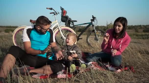 Manželský pár s dítětem na pozadí jejich jízdních kol. Mýdlové bubliny a zábavy