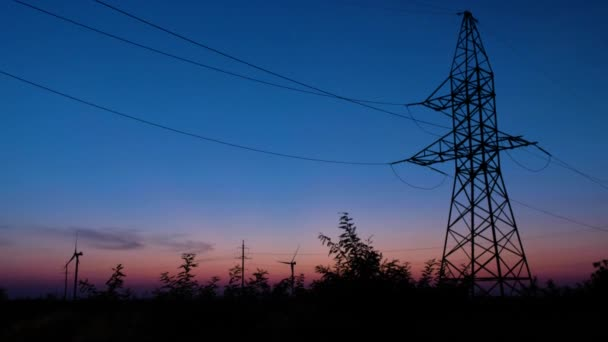 A silhouette of a power tower, standing against the last rays of setting sun