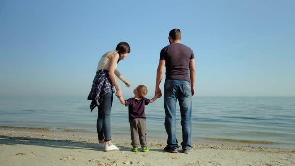 A happy family stands in front of the sea. Parents on the sea shore dandle their child. Slow motion