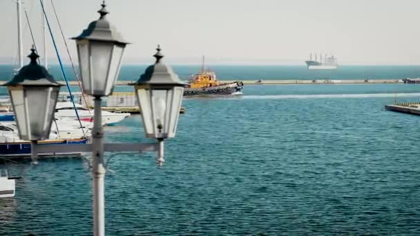 Lucerna detail proti moři. Lodě plující na moři. Rackové létají nad vodou