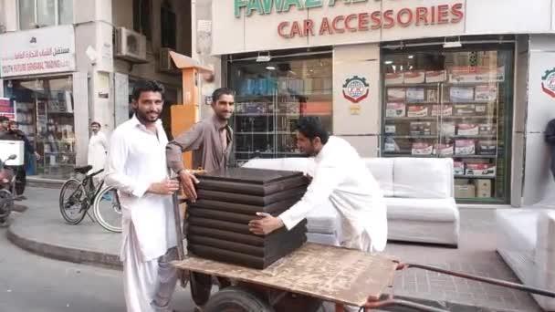 Arabian workers unload furniture greet tourists in street
