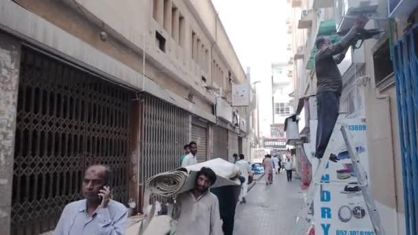 workers carry carpet flooring roll along pedestrian street