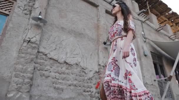 dívka Evropského vzhledu předává vedle obnovené starobylé budově Arabská