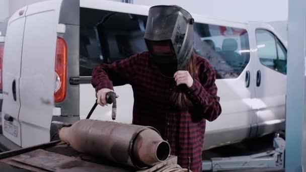 Dívka elektrická svářečka. Dívka v kostkované košili a ochranná helma elektrická svářečka svařuje kovu na auto tlumič na pozadí z auta na auto čerpací stanice.