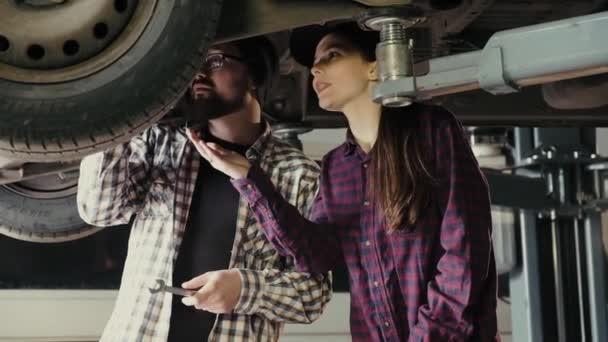 Muž, mentor, vysvětluje žena, začínajícího na čerpací stanici, principy opravy a údržbu automobilů suspenze.
