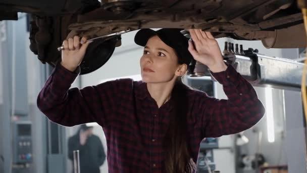 Dívka je automobilový mechanik, zabývající se oprava podvozku vozu v čerpací stanici