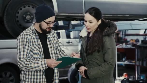 Krásná brunetka, klientské centrum služeb auto bere auto opravy a podepisuje dokumenty s automechanik.
