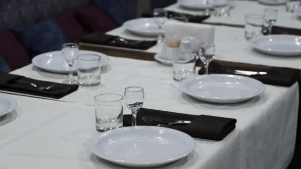 Table setting in a restaurant. Plates, glasses and other kitchen utensils stand on a long table.