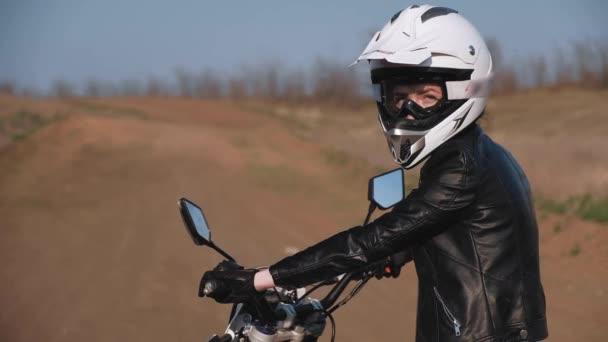Mladá dívka v půl otočka při pohledu na kameru, zatímco sedí na motorce