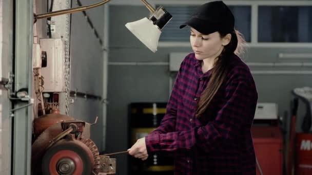 Mladá dívka na brusným stroji zostří nástroj.